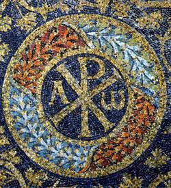 """Il """"Chrismòn"""", affiancato dall'alfa e dall'òmega, in un mosaico del V secolo nel mausoleo di Galla Placidia a Ravenna."""